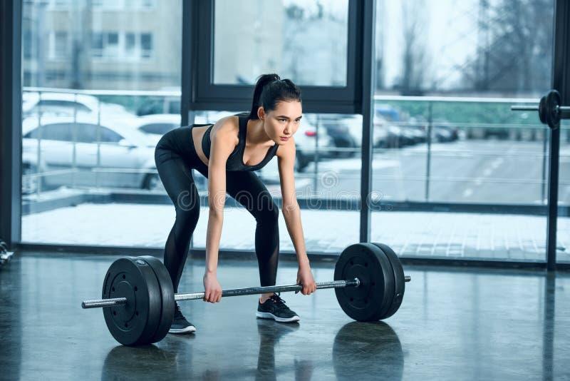 jonge atletische vrouw die barbell opheffen stock fotografie
