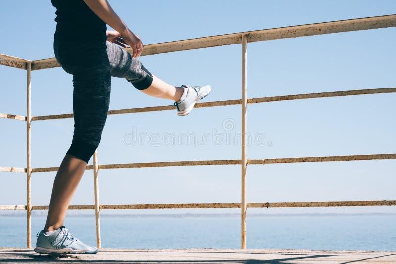 Jonge atletische vrouw die het uitrekken zich benen op het strand in m doen stock afbeeldingen