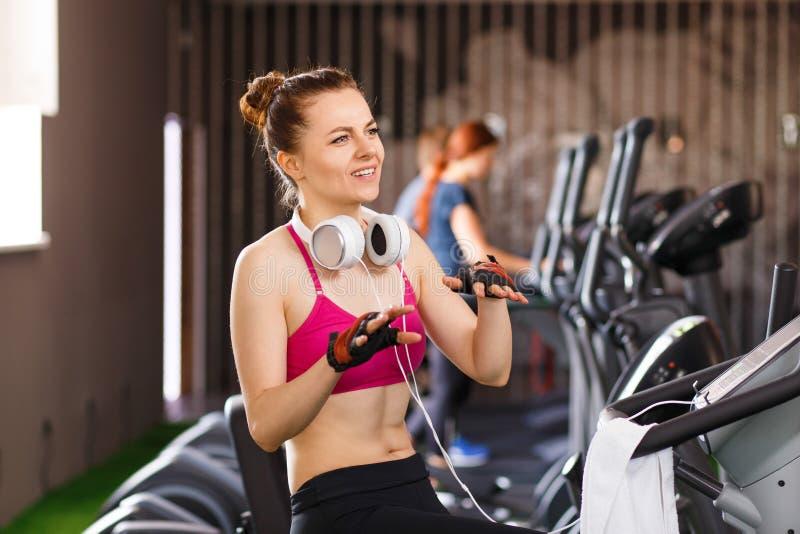 Jonge atletische vrouw die met trainer in gymnastiek spreken stock foto's