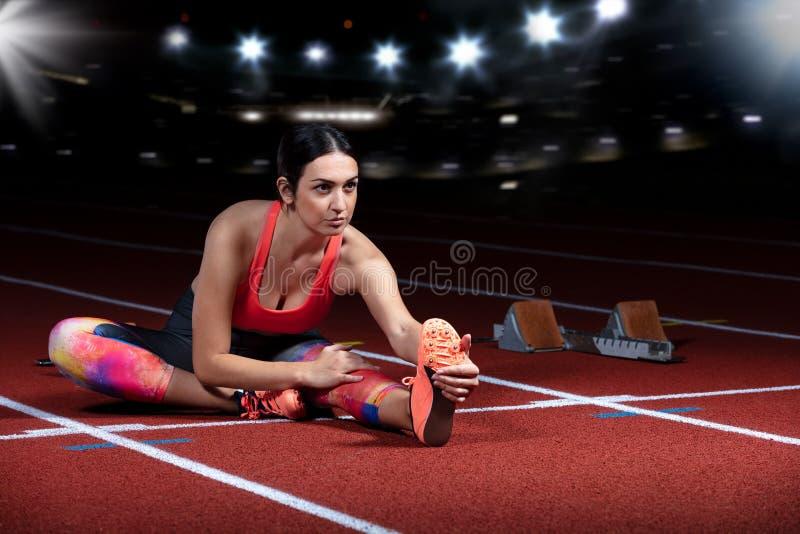 Jonge atletische vrouw die oefeningen op flexibiliteit doen het uitrekken van benen die spoorstadion, nacht met reflectors zitten stock fotografie