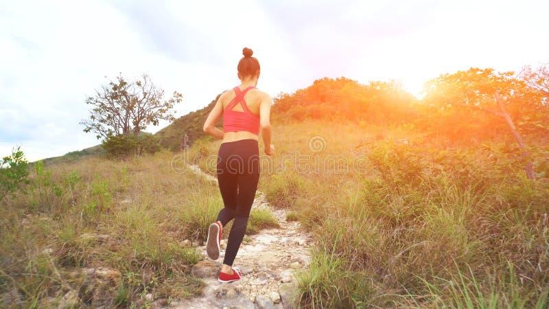 Jonge Atletische Vrouw die op Bergsleep lopen Zonsondergangtraining in Aard Geschikt meisje in roze hoogste looppas stock fotografie