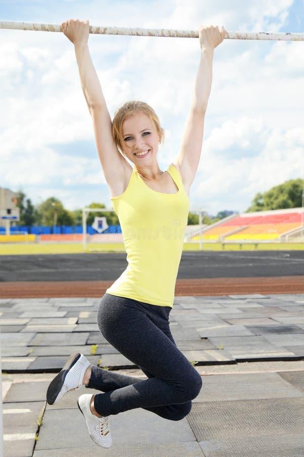 Jonge atletische vrouw die op rekstok houden stock fotografie