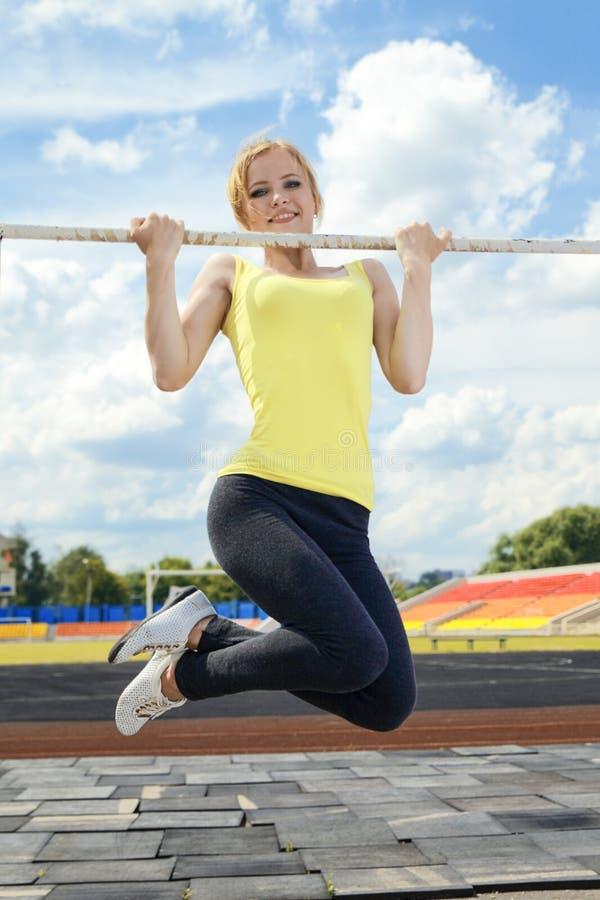 Jonge atletische vrouw die op rekstok houden stock afbeeldingen