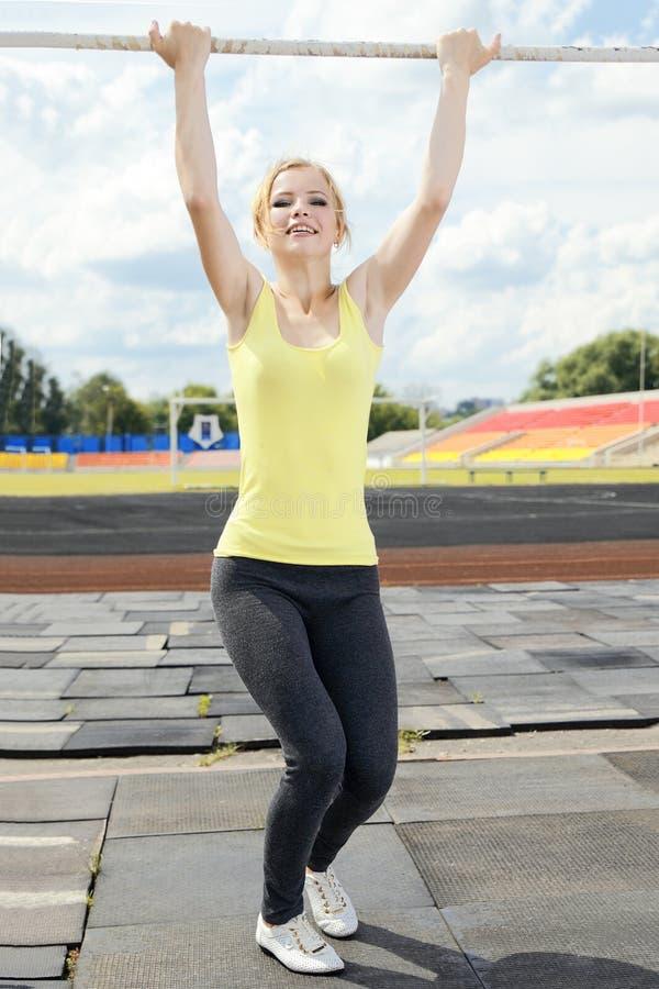 Jonge atletische vrouw die op rekstok houden royalty-vrije stock fotografie