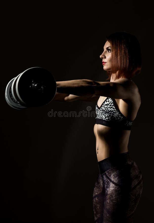 Jonge atletische vrouw in sportkleding met een dumbbellson een donkere achtergrond stock afbeeldingen