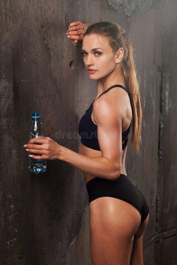 Jonge atletische vrouw in sportkledings drinkwater in studio tegen zwarte achtergrond Ideaal vrouwelijk sportencijfer Het verstan stock fotografie