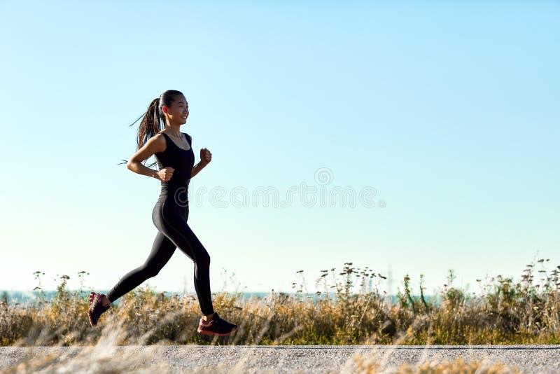 Jonge atletische vrouwenjogging op landelijke weg in vroege ochtend stock foto