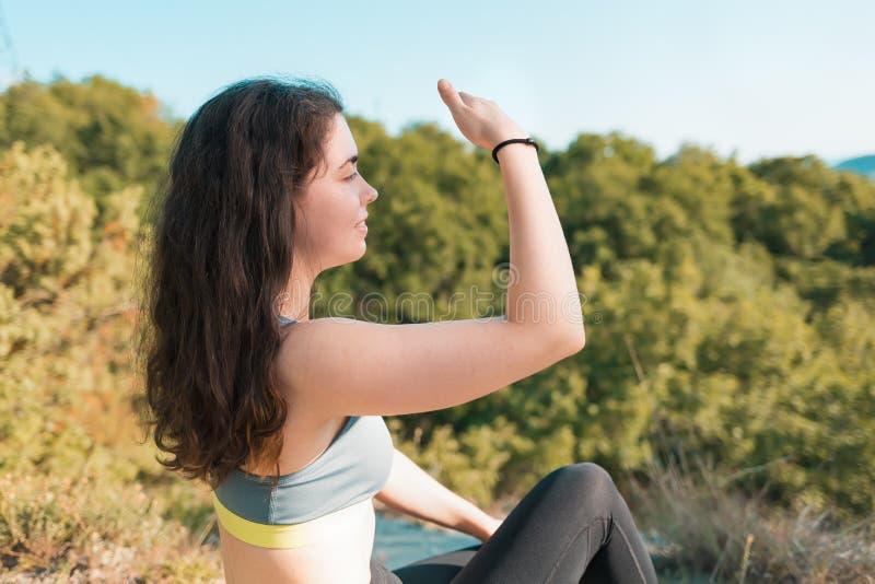 Jonge atletische vrouwenzitting die en de afstand rusten onderzoeken Bos op de achtergrond Sporten, fitness en gezond stock afbeelding