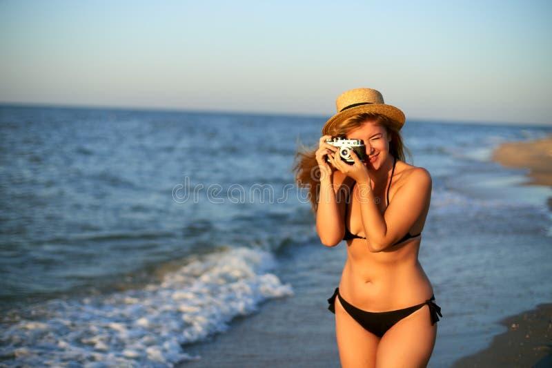 Jonge authentieke vrouw die met uitstekende retro filmcamera van tropisch strand op de zomervakantie genieten Vrouwelijke reis royalty-vrije stock afbeelding