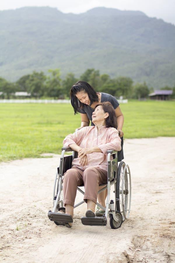 Jonge Aziaat neemt zorg de hogere vrouw met rolstoel stock foto