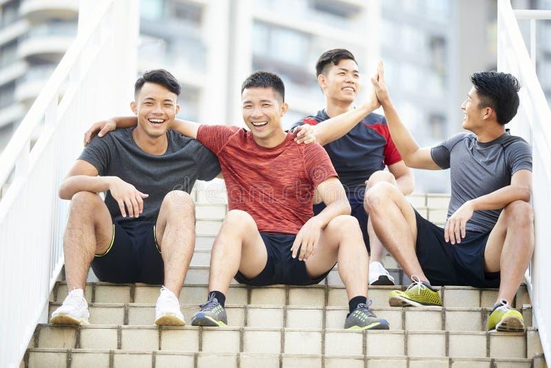 Jonge Aziatische atleten die na opleiding ontspannen royalty-vrije stock foto's
