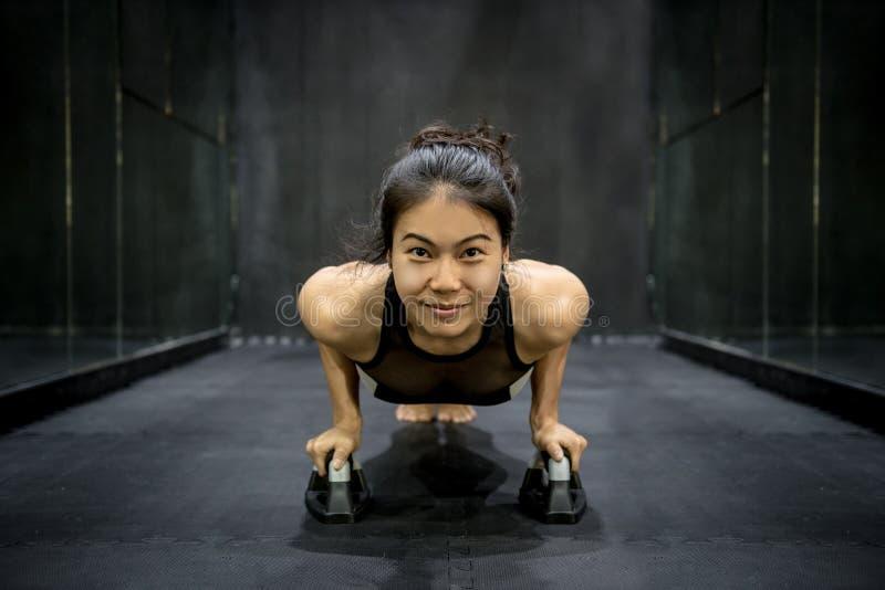 Jonge Aziatische atletenvrouw die duw omhoog op de vloer doen stock foto's