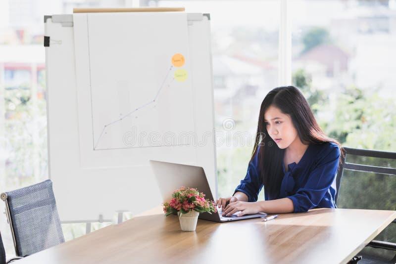 Jonge Aziatische bedrijfsdievrouw het werken aan laptop wordt geconcentreerd aan lusje stock afbeeldingen