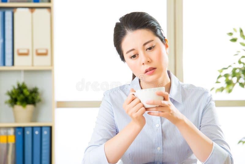 Jonge Aziatische bedrijfsdievrouw met ongemakkelijk wordt overgewerkt stock afbeelding