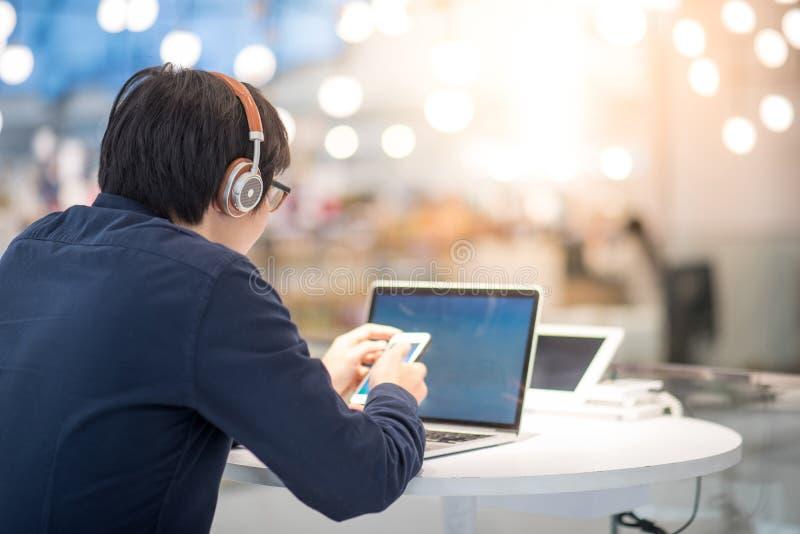 Jonge Aziatische bedrijfsmens die aan muziek luisteren terwijl het werken met l stock foto's
