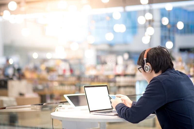 Jonge Aziatische bedrijfsmens die aan muziek luisteren terwijl het werken met l stock fotografie