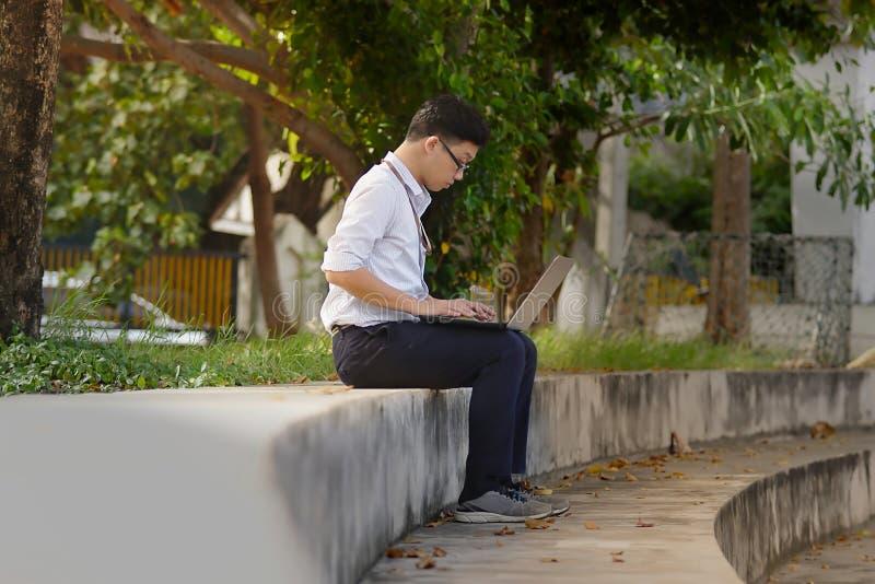Jonge Aziatische bedrijfsmens in formele slijtage die laptop voor zijn baan met behulp van bij het park tijdens ochtendtijd stock foto
