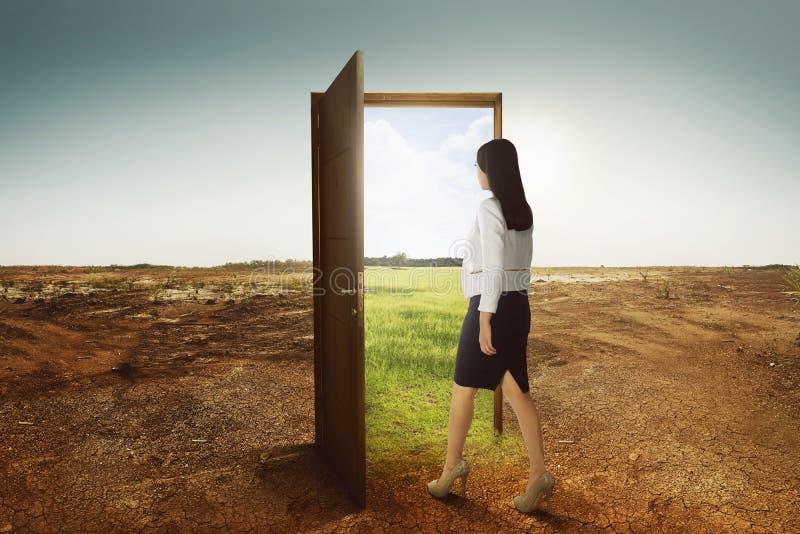 Jonge Aziatische bedrijfsvrouw die aan de open deur lopen die naar gre gaan stock afbeelding