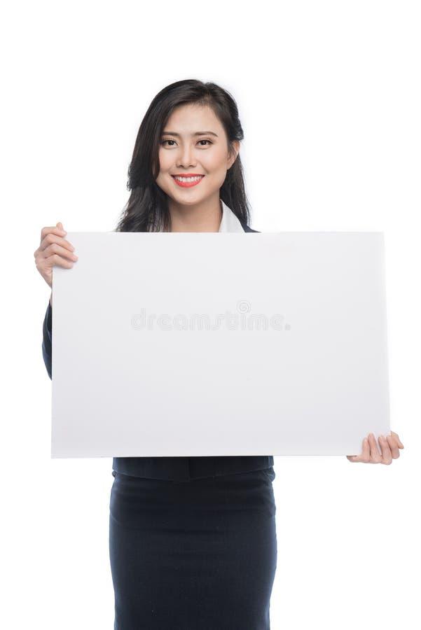 Jonge Aziatische bedrijfsvrouw die een witte die raad tonen op whi wordt geïsoleerd royalty-vrije stock fotografie