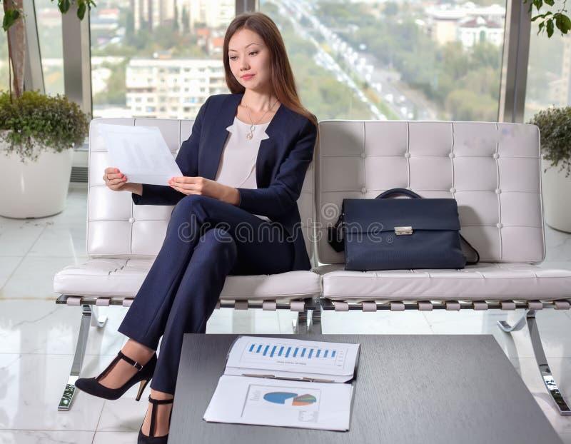 Jonge Aziatische bedrijfsvrouw die in kostuum de grafiek op het blad bekijken royalty-vrije stock afbeeldingen