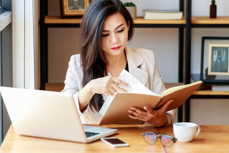Jonge Aziatische bedrijfsvrouw die op het werk werken mooie Aziatische vrouw in toevallig kostuum die met lezingsboek werken, stock foto
