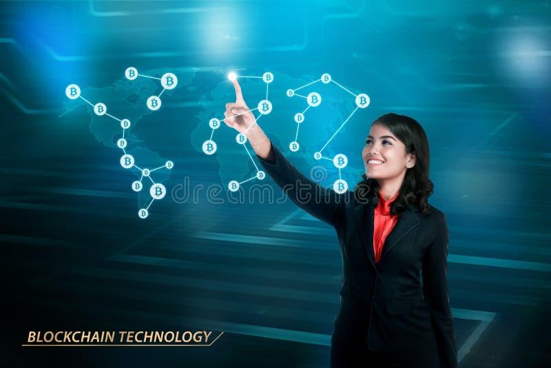 Jonge Aziatische bedrijfsvrouw wat betreft de kaart van het bitcoinnetwerk stock afbeelding