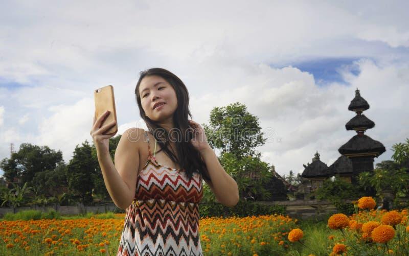 Jonge Aziatische Chinese toeristenvrouw die zelfportret selfie foto met mobiele telefoon op excursie nemen door mooi bloemengebie stock afbeelding