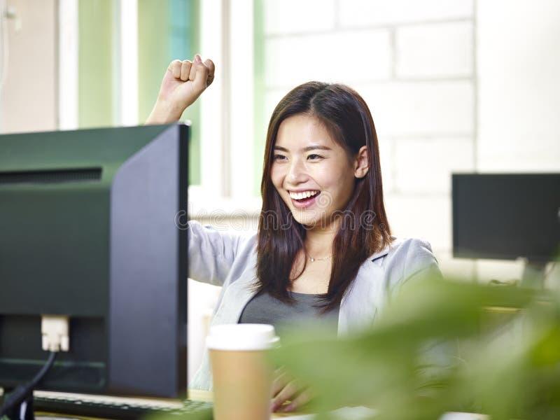 Jonge Aziatische die bureaudame bij goed nieuws wordt opgewekt royalty-vrije stock foto