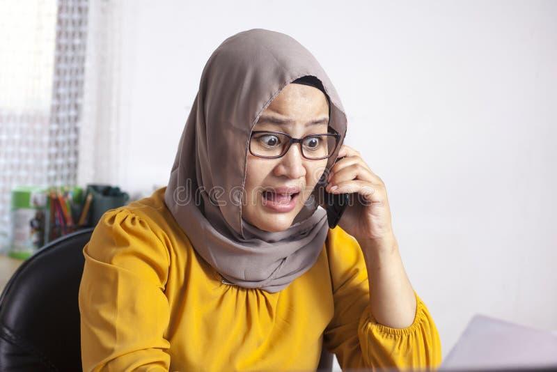 Jonge Aziatische die onderneemster door telefoongesprek wordt geschokt royalty-vrije stock foto's