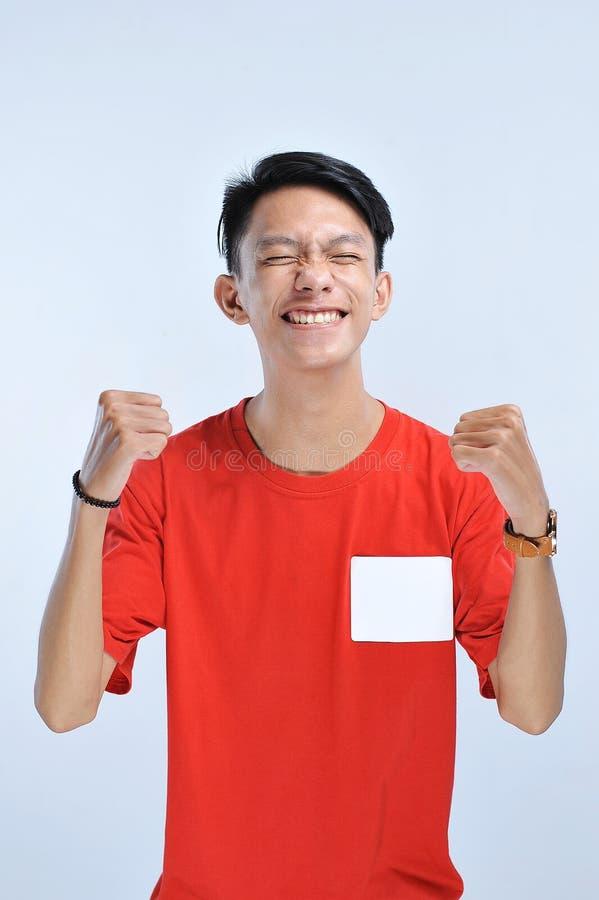 Jonge Aziatische gelukkig en opgewekte mens uitdrukkend het winnen gebaar Succesvol en vierend royalty-vrije stock fotografie