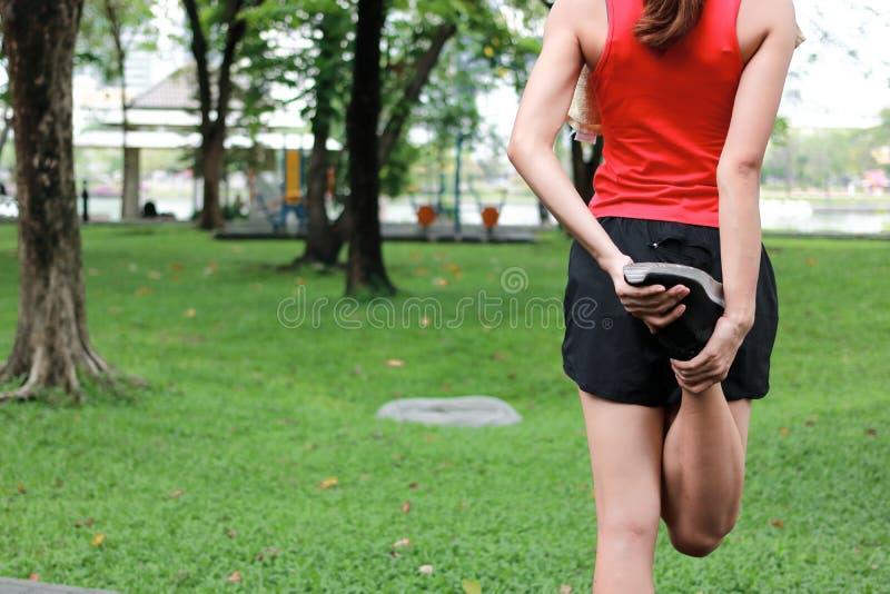 Jonge Aziatische geschiktheidsvrouw die haar benen uitrekken vóór looppas in park Geschiktheid en oefeningsconcept stock foto
