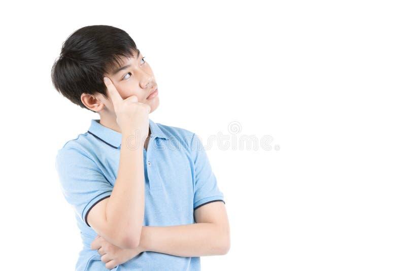 Jonge Aziatische jongen die over witte achtergrond denken stock afbeeldingen