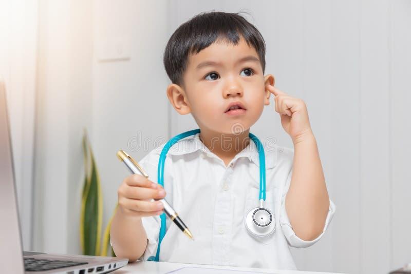 Jonge Aziatische jongen speelarts en het houden van pen terwijl het denken royalty-vrije stock afbeelding