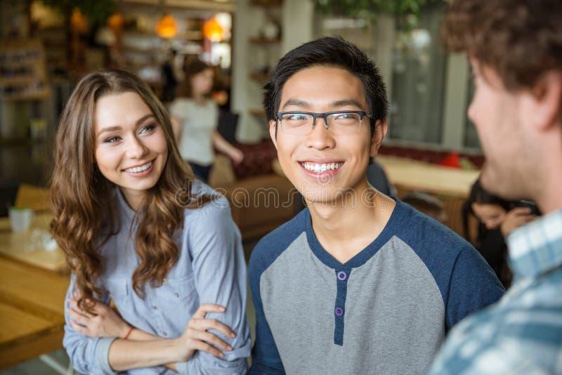 Jonge Aziatische man en vrolijke vrouw die aan hun vriend luisteren royalty-vrije stock foto