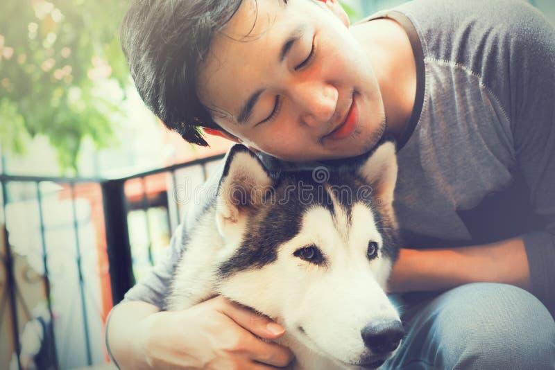 Jonge Aziatische mannelijke hondeigenaar die en het Husky Siberian-hondhuisdier met liefde en zorg koesteren omhelzen royalty-vrije stock afbeelding