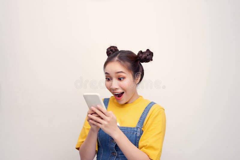 Jonge Aziatische meid die belt en verrast is stock afbeelding