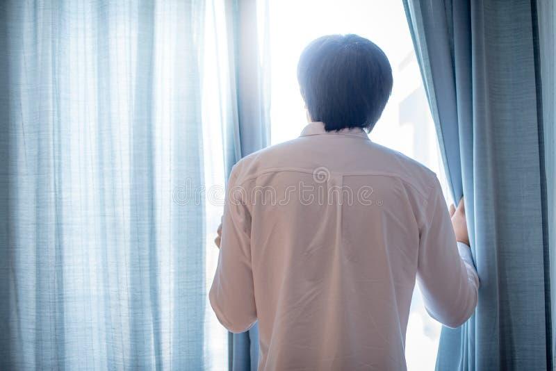 Jonge Aziatische mens die blauw gordijn in woonkamer openen royalty-vrije stock foto's