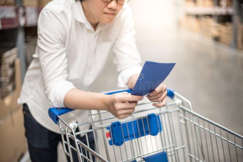 Jonge Aziatische mens die de het winkelen lijst in pakhuis controleren royalty-vrije stock fotografie