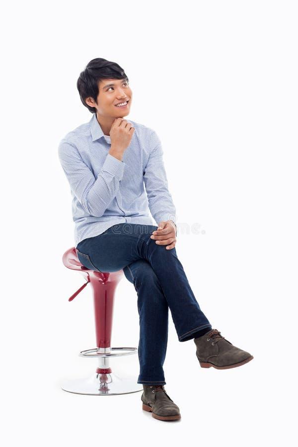 Jonge Aziatische mens die op de stoel denken. stock afbeelding