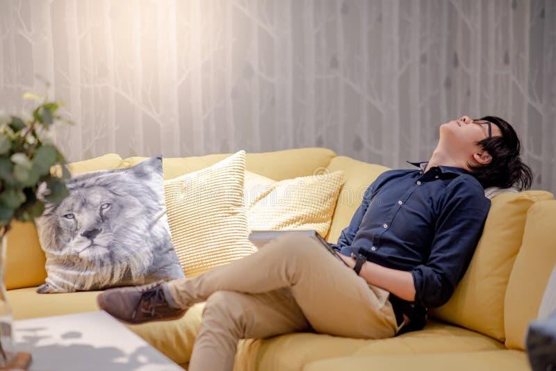 Jonge Aziatische mens die een dutje nemen terwijl het lezen van boek op bank royalty-vrije stock afbeeldingen