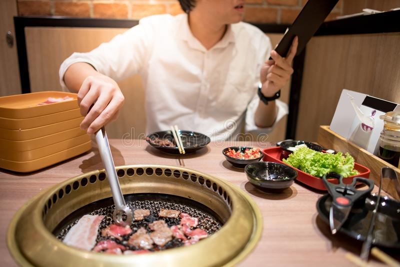Jonge Aziatische mens die Koreaans Barbecuebuffet in restaurant eten stock foto