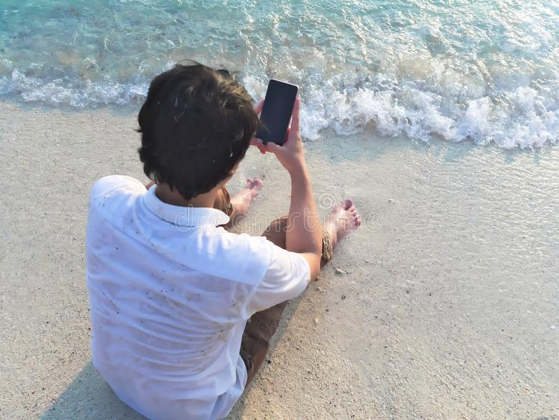 Jonge Aziatische mens die mobiele slimme telefoon op het zandige strand met behulp van Het concept van de zomervakanties royalty-vrije stock afbeeldingen