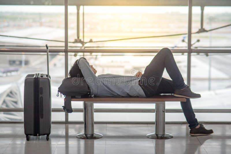Jonge Aziatische mens die op bank in luchthaventerminal liggen stock afbeelding