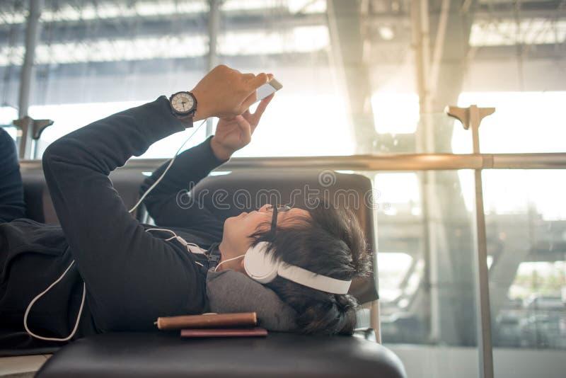 Jonge Aziatische mens die smartphone in luchthaventerminal gebruiken royalty-vrije stock afbeelding