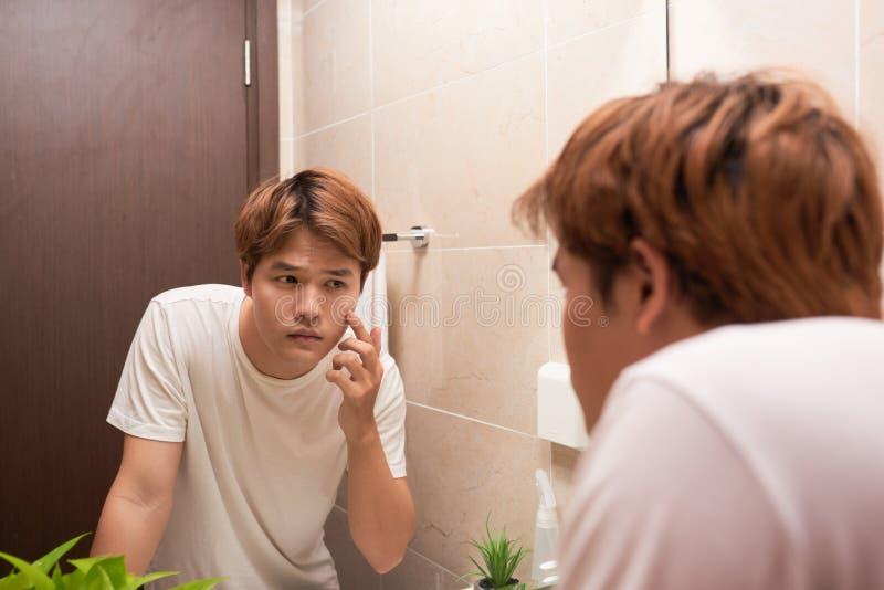 Jonge Aziatische mens die in spiegel kijken en zijn huid in bathr controleren royalty-vrije stock foto