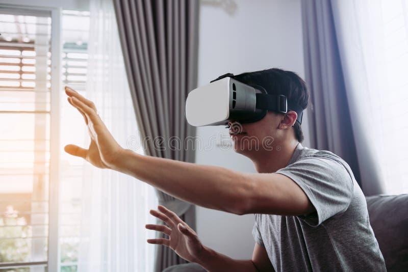 Jonge Aziatische mens die virtuele werkelijkheidsglazen dragen bij woonkamer voor het bewonderen van virtuele werkelijkheid stock foto's