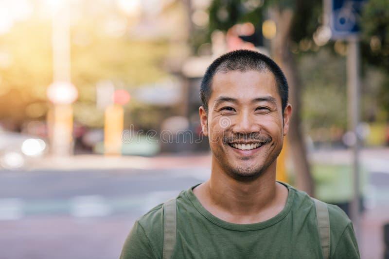 Jonge Aziatische mens die vol vertrouwen op een stadsstraat glimlachen stock afbeelding