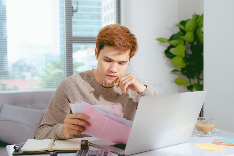 Jonge Aziatische mens die zijn rekeningen thuis in de woonkamer betalen royalty-vrije stock fotografie