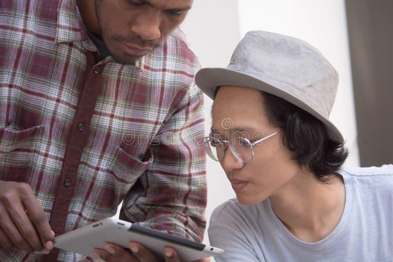 Jonge Aziatische mens met hoed en glazen die terwijl iets met vriend bespreek die een tablet tonen glimlachen royalty-vrije stock foto's
