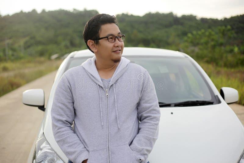 Jonge Aziatische Mens Smling voor Zijn Auto Openlucht in Ochtend stock afbeelding